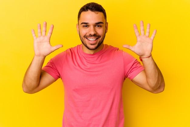 手で 10 番を示す黄色の背景に分離された若い白人男性。