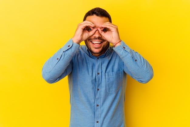 Молодой кавказский человек изолирован на желтом фоне, показывая хорошо знаком над глазами