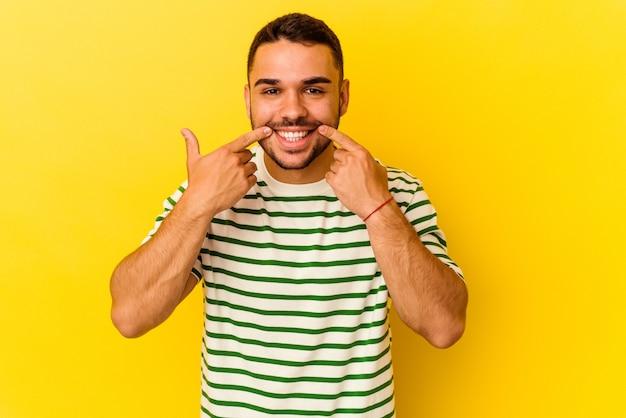 입에서 손가락을 가리키는 노란색 배경 미소에 고립 된 젊은 백인 남자.