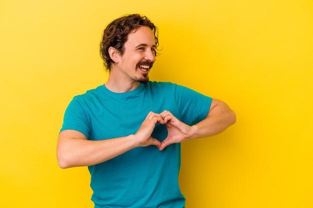웃 고 손으로 심장 모양을 보여주는 노란색 배경에 고립 된 젊은 백인 남자.