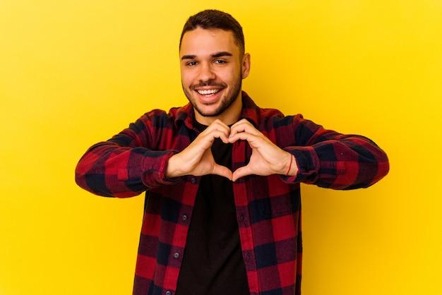 笑顔と手でハートの形を示す黄色の背景に分離された若い白人男性。
