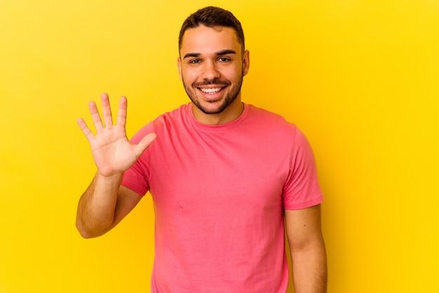 黄色の背景に孤立した若い白人男性は、指で5番を示して陽気に笑っています。