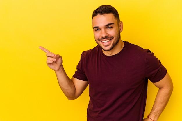 유쾌 하 게 집게 손가락으로 가리키는 웃 고 노란색 배경에 고립 된 젊은 백인 남자.