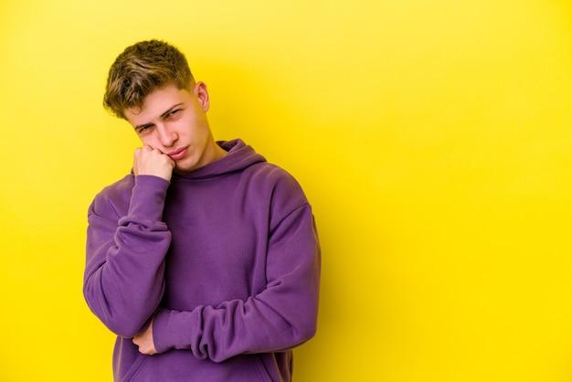 Молодой человек кавказской изолирован на желтом фоне, который чувствует себя грустным и задумчивым, глядя на пространство для копирования.