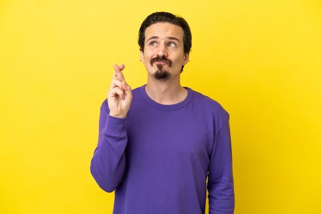 Молодой кавказский человек изолирован на желтом фоне со скрещенными пальцами и желает лучшего