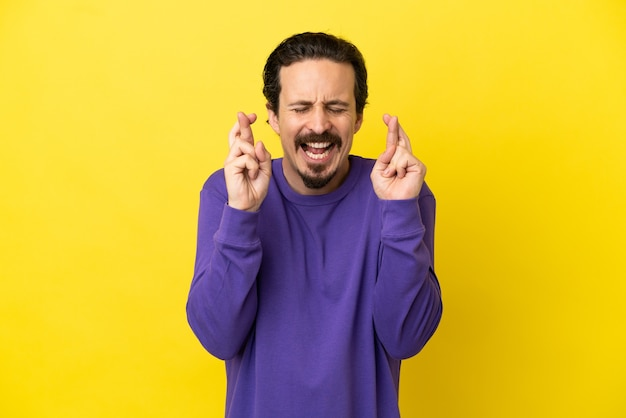 Молодой человек кавказской изолирован на желтом фоне со скрещенными пальцами