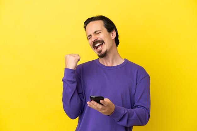 Молодой человек кавказской изолирован на желтом фоне с телефоном в позиции победы