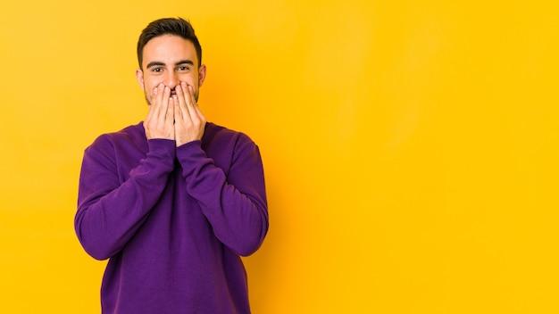 黄色いbakgroundで孤立した若い白人男性は、何かについて笑い、手で口を円錐形にします。