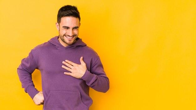 心に手を置いて笑って、幸せの概念、黄色のbakgroundに孤立した若い白人男性。