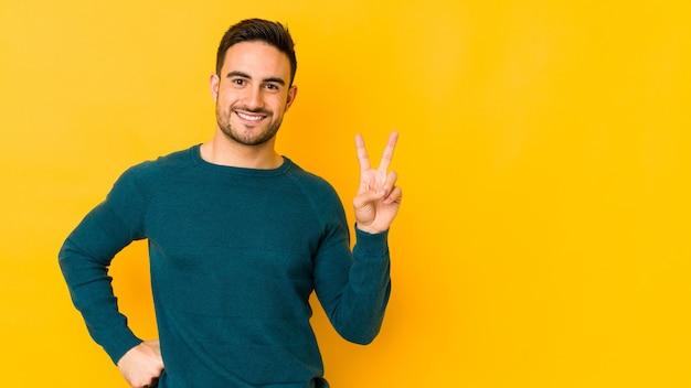 Молодой кавказский человек, изолированные на желтом bakground, показывая номер два пальцами.