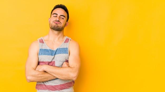 繰り返しの仕事にうんざりしている黄色のbakgroundに孤立した若い白人男性。