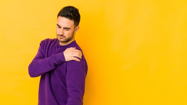 어깨 통증이있는 노란색에 고립 된 젊은 백인 남자.