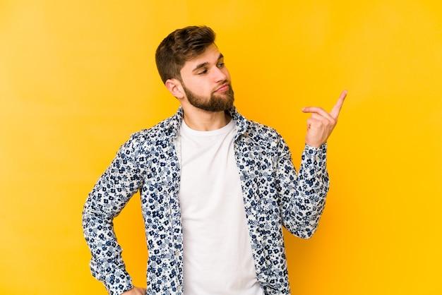 Молодой кавказский мужчина изолирован на желтом, указывая пальцем на вас, как будто приглашая подойти ближе.