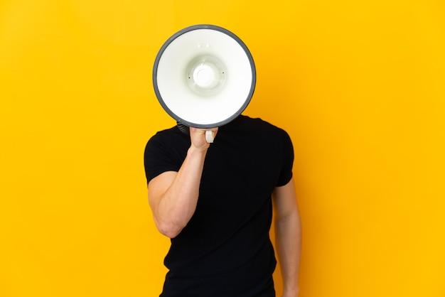 뭔가를 발표하기 위해 확성기를 통해 노란색 소리에 고립 된 젊은 백인 남자