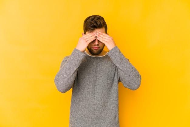 顔の前に触れて、頭痛を持っている黄色い空間に孤立した若い白人男性。