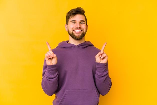 Молодой кавказский человек, изолированный на желтом пространстве, показывает двумя указательными пальцами вверх, показывая пустое пространство.
