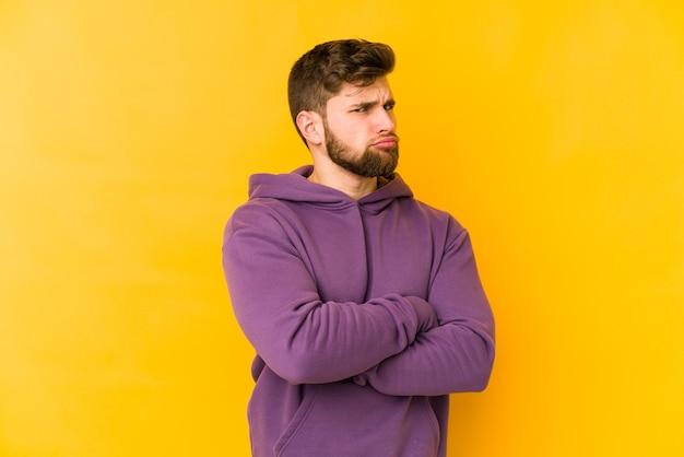 Молодой человек кавказской изолирован на желтом подозрительно, неуверенно, исследует вас.