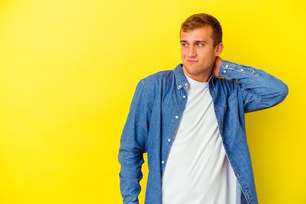 頭の後ろに触れて、考えて、選択をする黄色で孤立した若い白人男性。