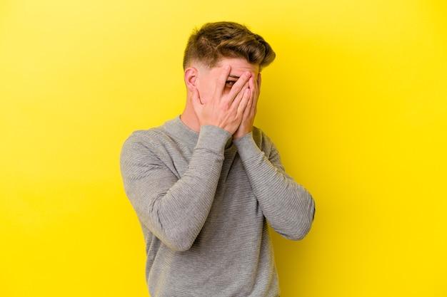 黄色い壁に孤立した若い白人男性が指でカメラを瞬き、恥ずかしい顔を覆っている