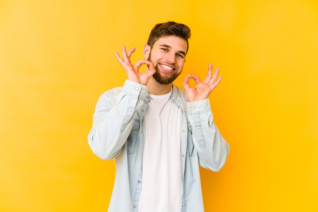 黄色い壁に孤立した若い白人男性は、陽気で自信を持って大丈夫なジェスチャーを示しています。