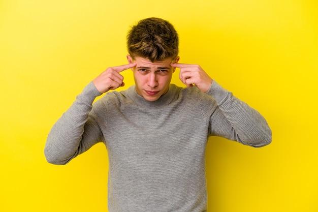 노란색 벽에 고립 된 젊은 백인 남자는 머리를 가리키는 집게 손가락을 유지하는 작업에 집중했다.