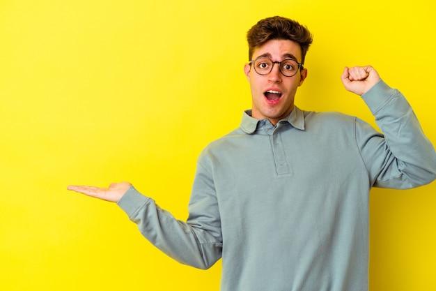 노란색 벽에 고립 된 젊은 백인 남자 손바닥에 복사 공간을 보유하고 뺨에 손을 유지