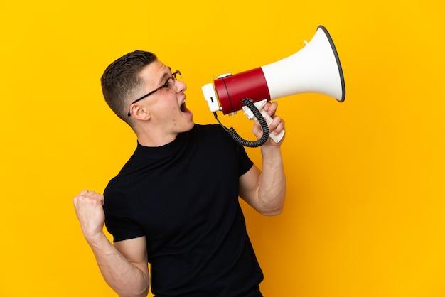 측면 위치에서 뭔가를 발표하기 위해 확성기를 통해 외치는 노란색 벽에 고립 된 젊은 백인 남자