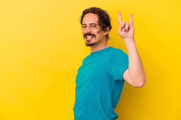 혁명 개념으로 뿔 제스처를 보여주는 노란색 벽에 고립 된 젊은 백인 남자.