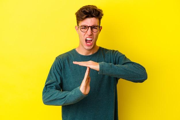 タイムアウトジェスチャーを示す黄色の壁に分離された若い白人男性