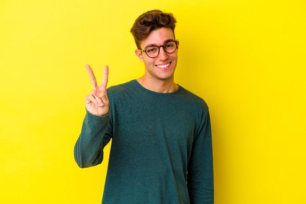 指で2番目を示す黄色の壁に分離された若い白人男性