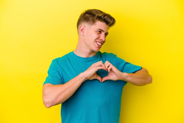 웃 고 손으로 심장 모양을 보여주는 노란색 벽에 고립 된 젊은 백인 남자