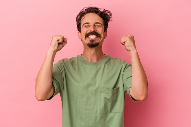 Young caucasian man isolated on pink background celebrating a victory, passion and enthusiasm, happy expression.