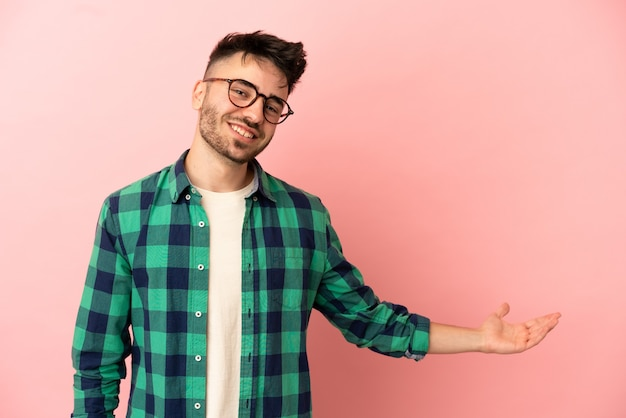 Young caucasian man isolated on pink background extending hands to the side for inviting to come