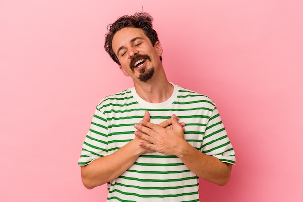 Young caucasian man isolated on pink background has friendly expression, pressing palm to chest. love concept.