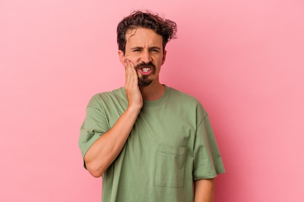 Young caucasian man isolated on pink background having a strong teeth pain, molar ache.