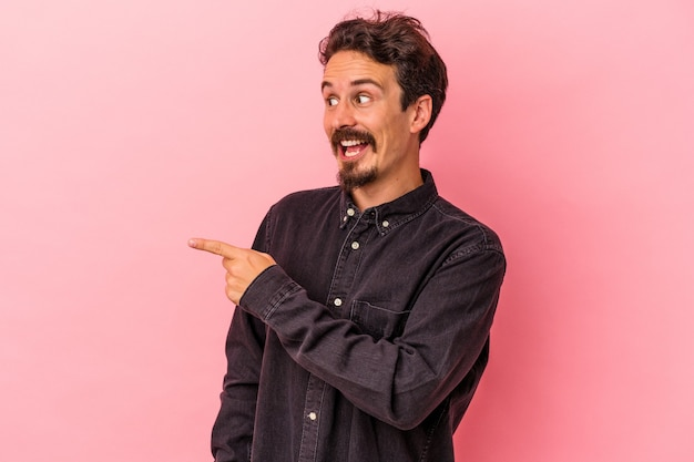 Young caucasian man isolated on pink background looks aside smiling, cheerful and pleasant.