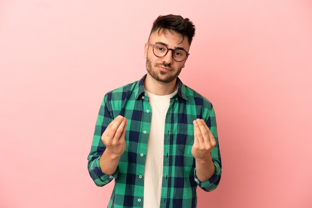 Young caucasian man isolated on pink background making money gesture but is ruined
