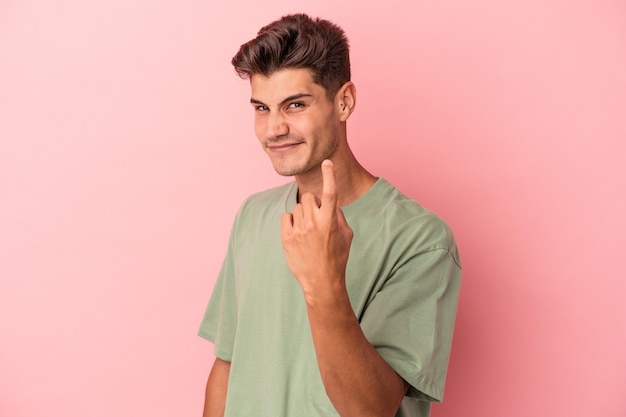 Young caucasian man isolated on pink background pointing with finger at you as if inviting come closer.