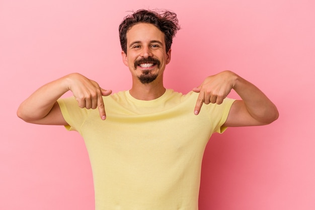 Young caucasian man isolated on pink background points down with fingers, positive feeling.