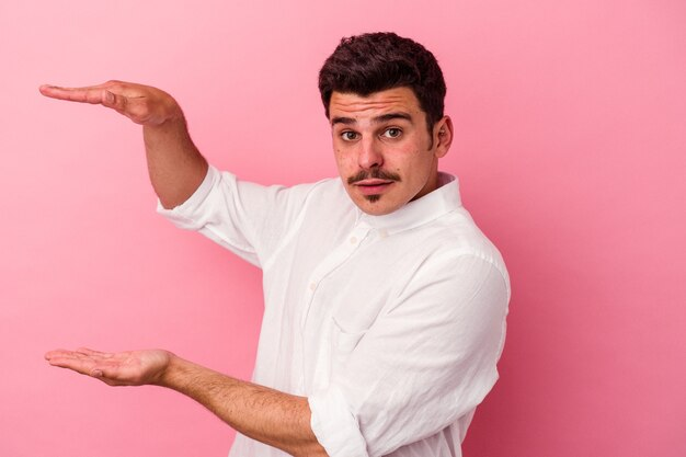 Young caucasian man isolated on pink background shocked and amazed holding a copy space between hands.