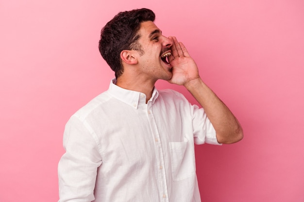 Young caucasian man isolated on pink background shouting and holding palm near opened mouth.