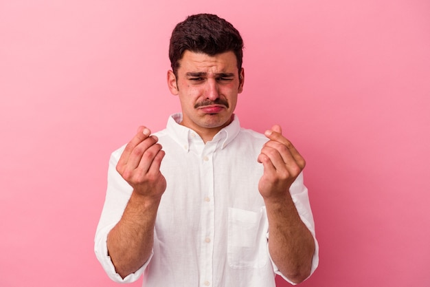 Young caucasian man isolated on pink background showing that she has no money.