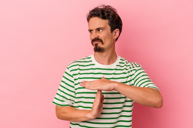 Young caucasian man isolated on pink background showing a timeout gesture.