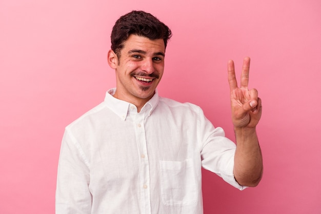 Young caucasian man isolated on pink background showing victory sign and smiling broadly.