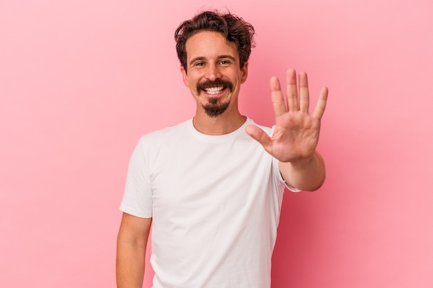 Young caucasian man isolated on pink background smiling cheerful showing number five with fingers.
