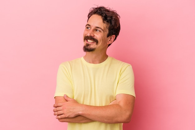 Young caucasian man isolated on pink background smiling confident with crossed arms.