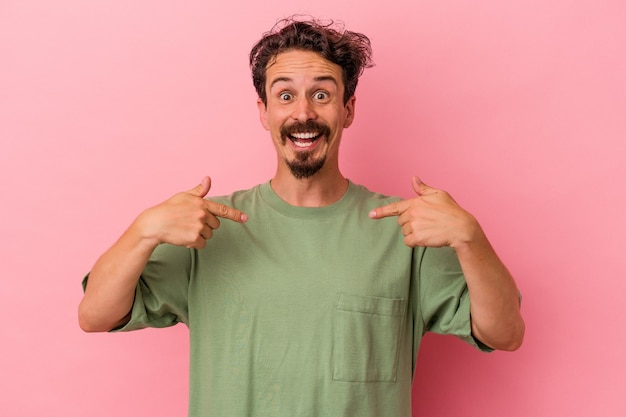 Young caucasian man isolated on pink background surprised pointing with finger, smiling broadly.