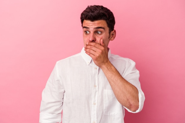 Young caucasian man isolated on pink background thoughtful looking to a copy space covering mouth with hand.
