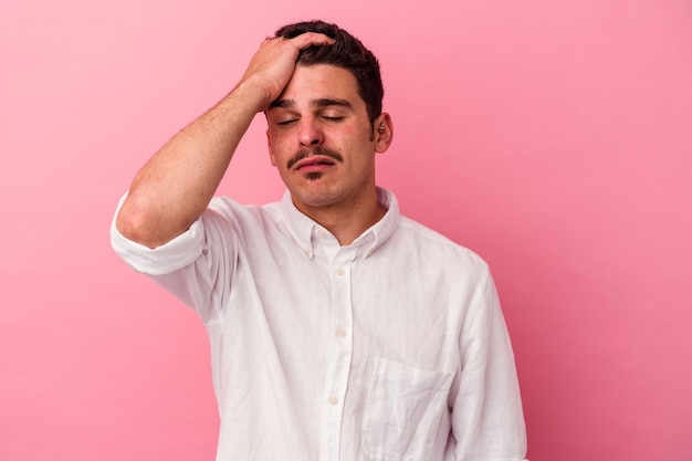 Young caucasian man isolated on pink background tired and very sleepy keeping hand on head.