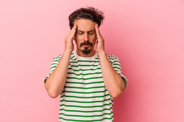 Young caucasian man isolated on pink background touching temples and having headache.